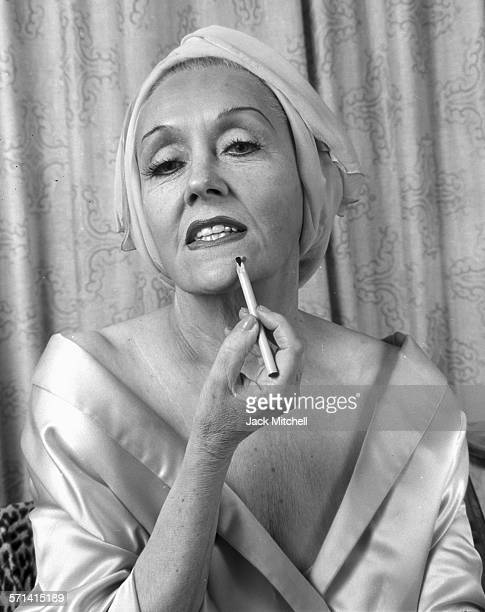 Actress Gloria Swanson photographed applying makeup at her home in New York City in 1965