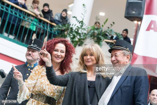 Actress Goldie Hawn conducts a band next to Christina Lugner and Richard Lugner during an autograph session at Lugner City on February 22 2017 in...