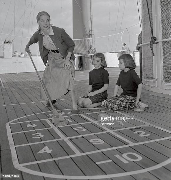 Actress Grace Kelly aboard the liner Constitution on her way to Monaco to be married to Prince Rainier She is seen here playing shuffleboard with two...