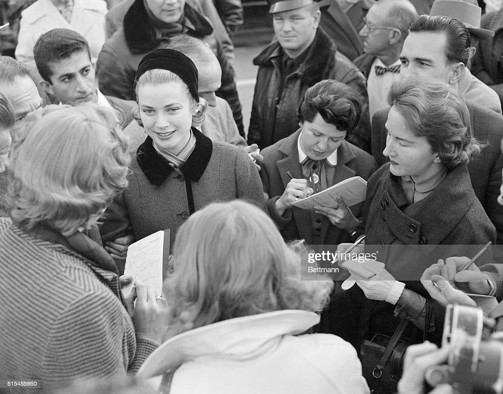 Actress Grace Kelly (in black hat) is mobbed by reporters and Hollywood columnists as she arrives by train at Pasadena, January 10th. Studio press agents tried to whisk Miss Kelly away, but the mass of newsmen won a brief interview. She said that her wedding to prince Rainier III of Monaco will be 'formal with a mass, and after Easter,' but did not say where it would take place.