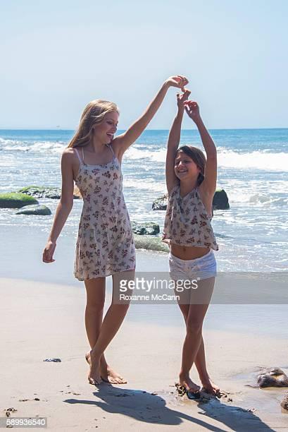 Actress Grace Van Dien cast member of the Netflix series The Greenhouse dances with sister Celeste Van Dien on the beach on June 22 2015 in Malibu...