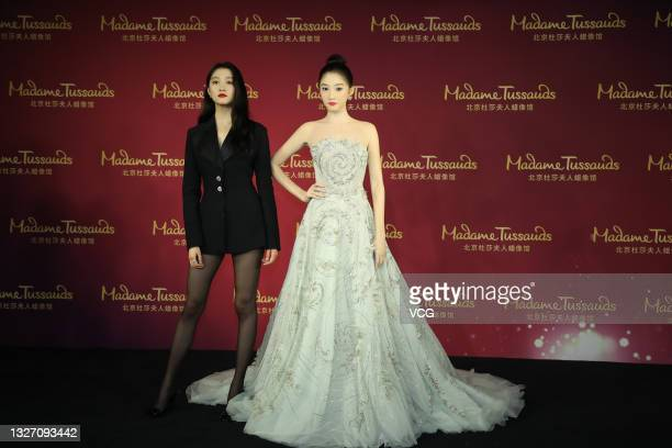 Actress Guan Xiaotong poses with her wax figure during the unveiling ceremony at Madame Tussauds Beijing on July 5, 2021 in Beijing, China.