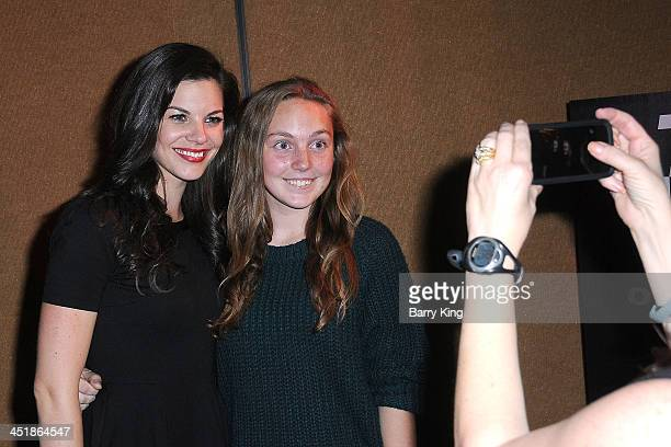 Actress Haley Webb poses with a fan at the 20th Century Fox Home Entertainment and MTV Network Teen Wolf fan appreciation event on November 23 2013...