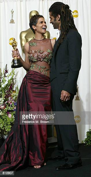 Actress Halle Berry and her husband musician Eric Benet pose with her Best Actress in a Leading Role Award for 'Monster's Ball' backstage during the...
