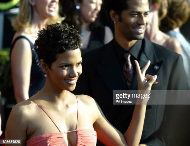 Actress Halle Berry flashes a peace sign as she arrives on the red carpet for the 9th annual Screen Actors Guild Awards at the Shrine Auditorium in...