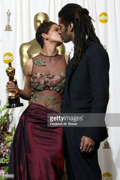 Actress Halle Berry kisses her husband musician Eric Benet as she holds her Oscar for Best Actress In A Leading Role backstage during the 74th Annual...