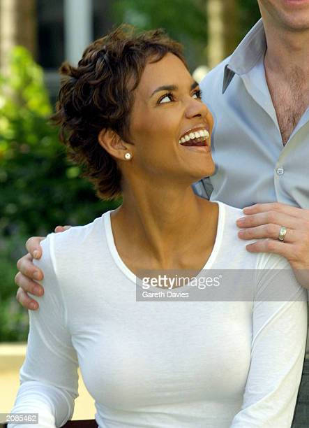 Actress Halle Berry laughs with Hugh Jackman for photographers at a photocall for her new film Swordfish in Canary Wharf London on June 25 2001