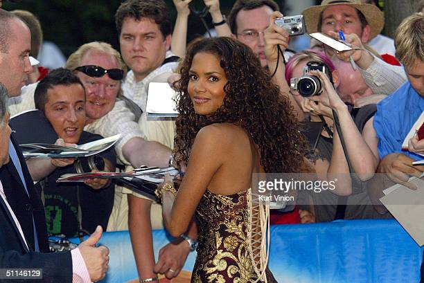 """Actress Halle Berry signs autographs for waiting fans as she attends the German premiere of her new film """"Catwoman"""" at the Cinemax August 5, 2004 in..."""