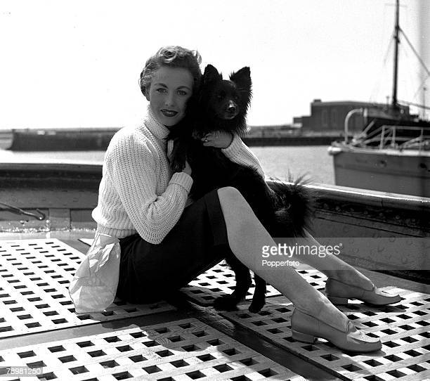 1952 Actress Hazel Court with a dog on the the ship's deck in between takes of the film Ghost ship