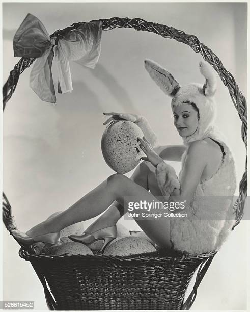 Actress Heather Angel poses as the Easter Bunny in a basket full of Easter eggs