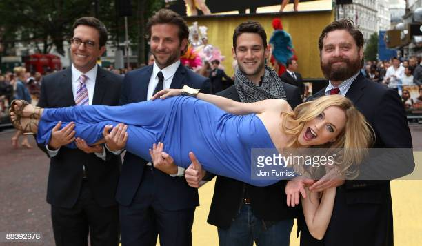 Actress Heather Graham is carried by director Todd Phillips and actors Bradley Cooper Justin Bartha and Zach Galifianakis as they attend 'The...