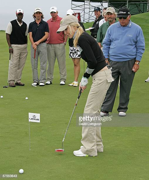 Actress Heather Locklear putts as actor Don Cheadle, musician Kenny G, actor Michael Douglas and golf instructor Butch Harmon watch at the 8th annual...