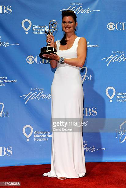 Actress Heather Tom poses with the Outstanding Supporting Actress award in the press room at the 38th Annual Daytime Entertainment Emmy Awards held...