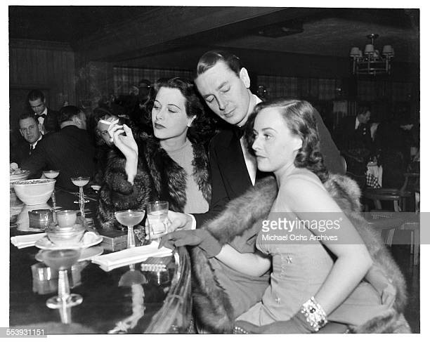 Actress Hedy Lamarr smokes a cigarette at a bar with actress Paulette Goddard during an event in Los Angeles California