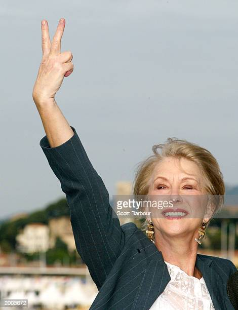 Actress Helen Mirren puts two fingers up in jest as she poses for the cameras during a photocall for the film Calendar Girls on Carlton Beach during...