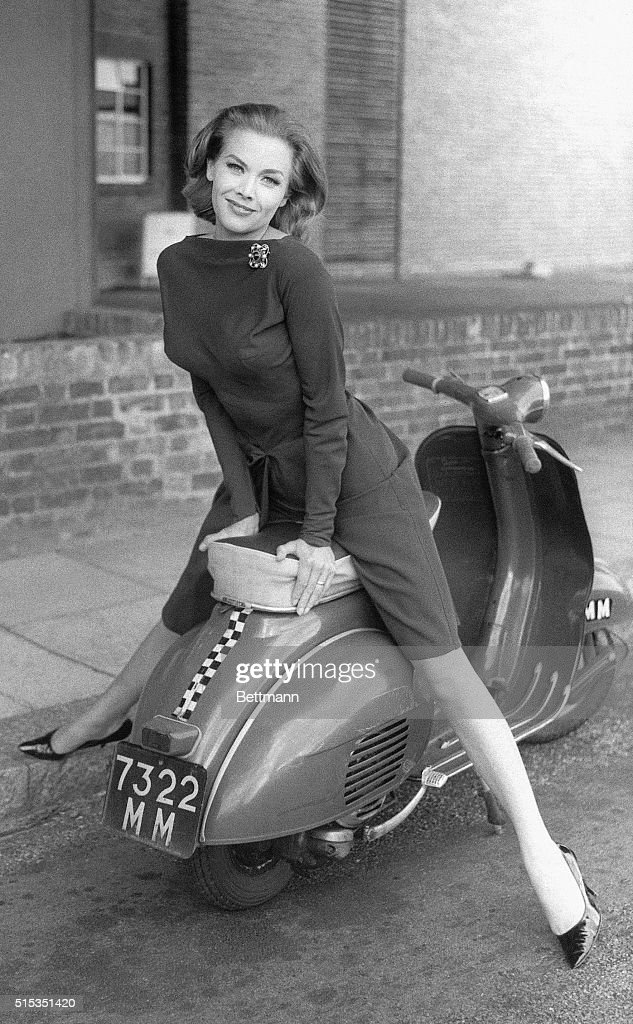 Actress Honor Blackman poses on a moped in a slender cocktail dress on the set of The Avengers television program in London. Blackman plays the role of Cathy Gale in the popular action series.