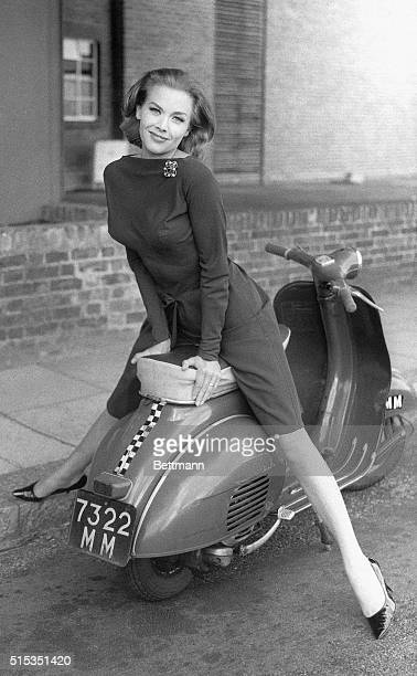 Actress Honor Blackman poses on a moped in a slender cocktail dress on the set of The Avengers television program in London. Blackman plays the role...