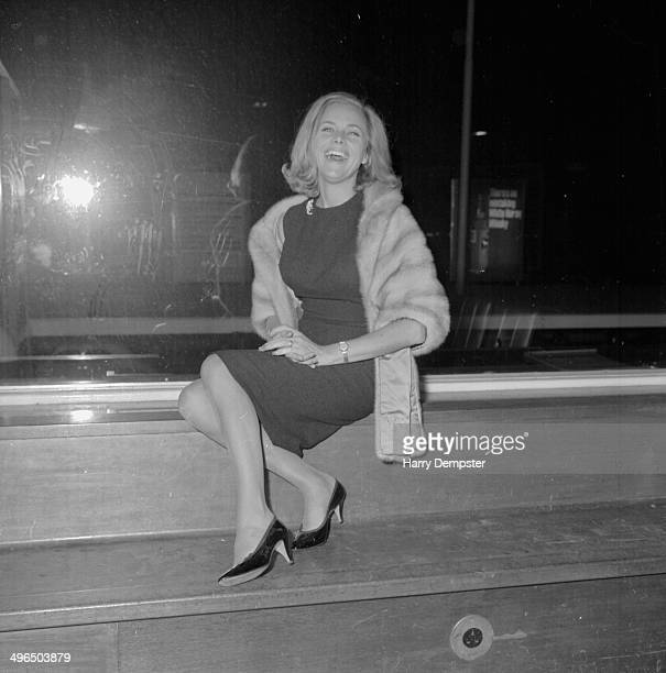 Actress Honor Blackman sitting on a wall wearing a fur coat, after attending a Liberal Party broadcast, London, October 7th 1964.