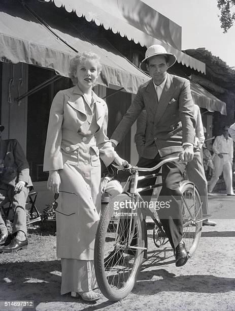 Actress Ida Lupino with movie producer Howard Hughes who is riding a bicycle in Palm Springs California
