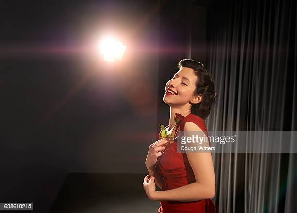 actress in red dress holding rose on stage. - schauspielerin stock-fotos und bilder