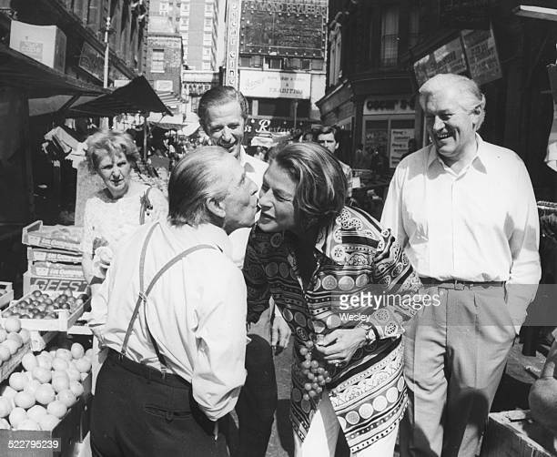 Actress Ingrid Bergman having her cheek kissed by stall holder Ben Williams as actors John McCallum and Michael Allinson look on at a local street...