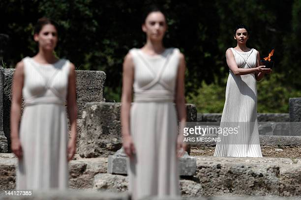 Actress Ino Menegaki acting as high priestess holds an urn carrying the Olympic Flame on May 10 2012 during the lighting ceremony in ancient Olympia...