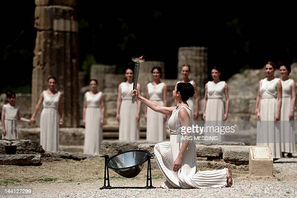 Actress Ino Menegaki acting as high priestess holds the torch carrying the Olympic Flame on May 10 2012 during the lighting ceremony in ancient...