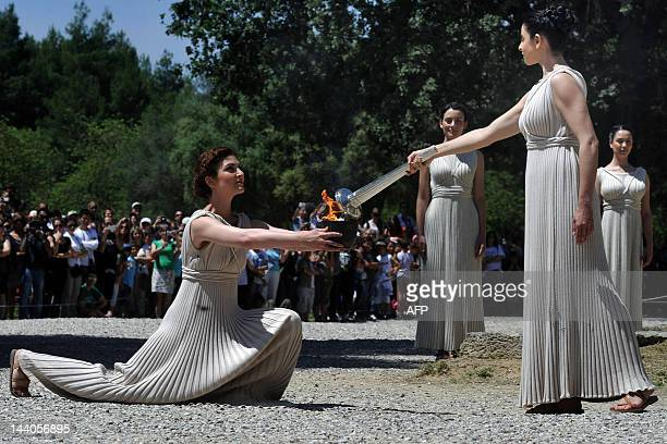 Actress Ino Menegaki acting as high priestess passes the Olympic flame to an other pristess on May 9 2012 during the lighting ceremony in ancient...