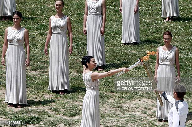 Actress Ino Menegaki acting as high priestess passes the Olympic flame to the first torch bearer swimmer Spyros Gianniotis on May 10 2012 during the...