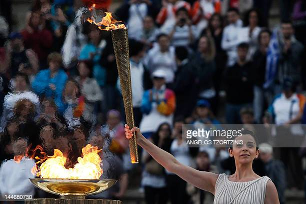 Actress Ino Menegaki in the role of the high priestess holds up the torch during the handover ceremony of the Olympic flame for the 2012 London...