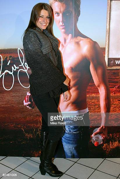 Actress Ivana Milicevic poses in front of a poster picturing cricketer Brett Lee during the official launch of the AceStar underwear range at Pink...