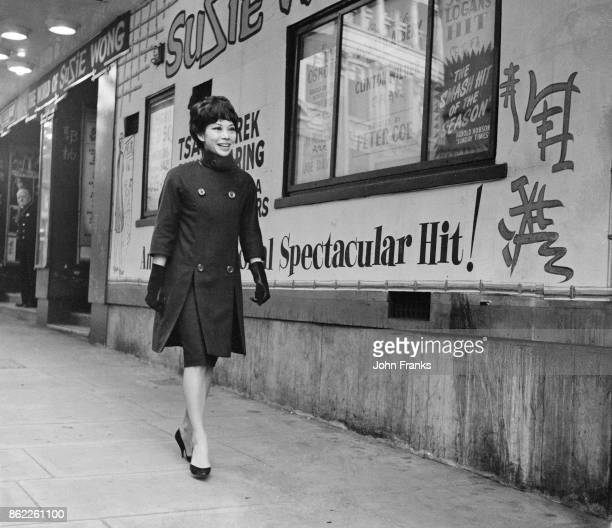 Actress Jacqueline Chan aka Jacqui Chan walks past posters of the play 'The World of Suzie Wong' outside the Prince of Wales Theatre in London 26th...