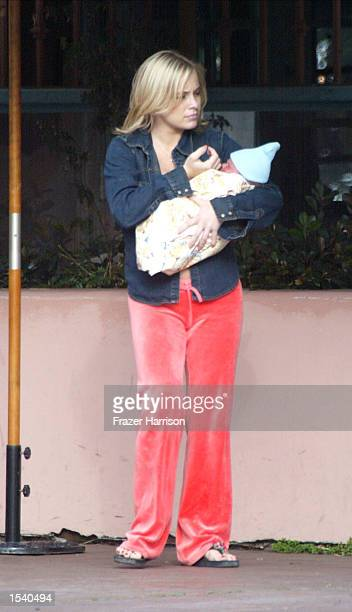 Actress Jaime Bergman waits for her car with her newborn baby outside The Ivy On The Shore restaurant after dining with her husband, actor David...