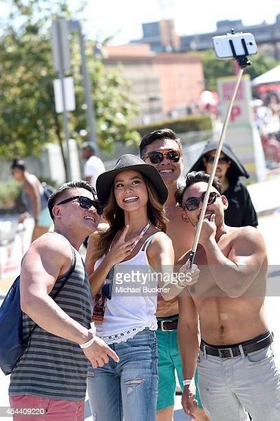 Actress Jamie Chung wearing American Eagle Sky High Demin takes a selfie with music fans at American Eagle Outfitters Celebrates the Budweiser Made...