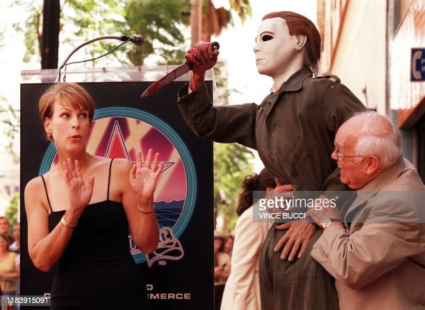 US actress Jamie Lee Curtis confronts a prop of the evil charcacter from her latest movie Halloween H20 held by honorary mayor of Hollywood Johnny...