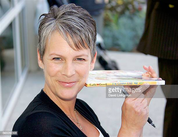 Actress Jamie Lee Curtis poses with one of her books during the grand opening of a new main library January 7 2006 in Santa Monica California...
