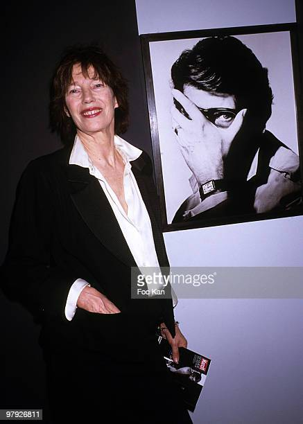 Actress Jane Birkin poses with a portrait of Yves St Laurent by Irving Penn at the Yves SaintLaurent Exhibition Launch Paris Fashion Week at Petit...