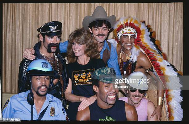 Actress Jane Fonda and singing group The Village People pose together during a disco party