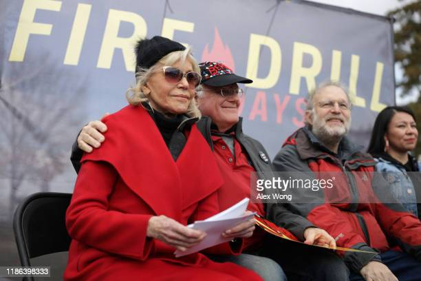 Actress Jane Fonda Ben Cohen and Jerry Greenfield cofounders of Ben Jerry's Ice Cream listen during a rally prior to a march from the US Capitol to...