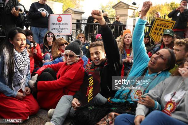 Actress Jane Fonda joins about 20 protesters as they sit in front of one of the White House gates during a Fire Drill Fridays rally protesting...