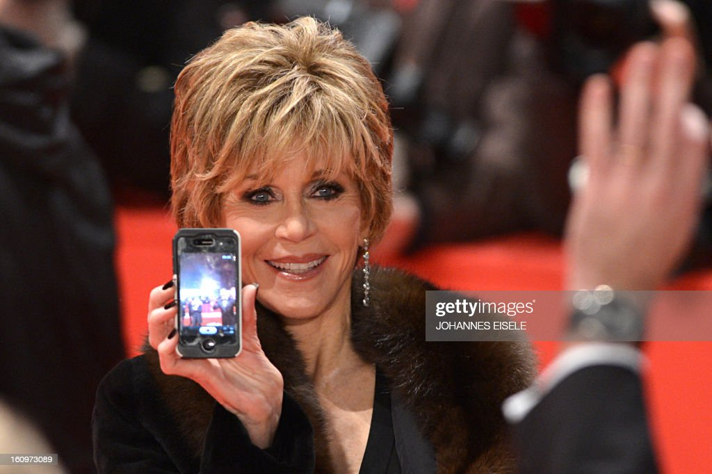 US actress Jane Fonda shows a picture she made with her mobile phone as she walks on the red carpet before a film screening at the 63rd Berlinale Film Festival on February 8, 2013. Guest attended the premiere screening of US director Gus van Sant's film 'Promised'. EISELE