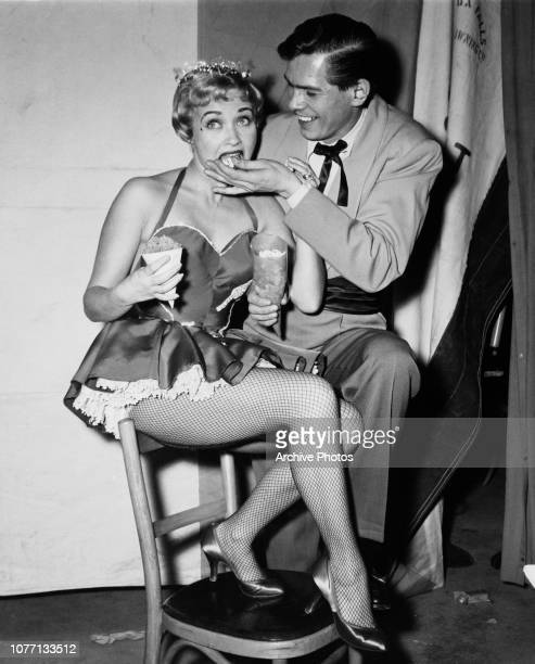 Actress Jane Powell and singer Johnnie Ray try the popcorn at a party thrown by actress and figure skater Sonja Henie circa 1950