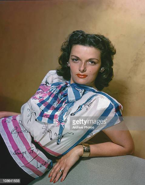 Actress Jane Russell pictured leaning back supported by her left arm USA circa 1955 Russell is wearing a white pink and blue printed top...