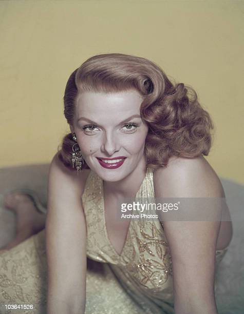 Actress Jane Russell pictured leaning forward, supported by both hands, USA, circa 1950. Russell, smiling, is wearing a yellow embroidered dress and...