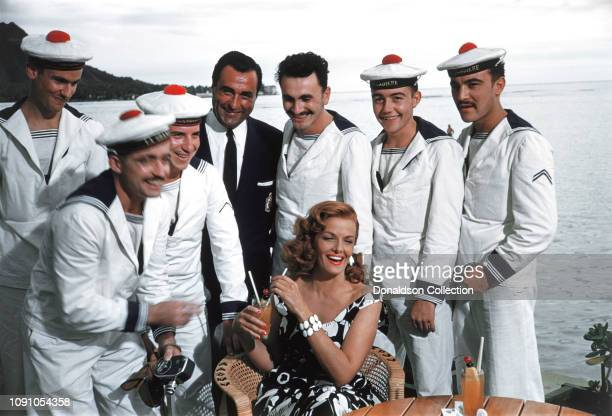 Actress Jane Russell poses for a photo with French sailors on the set of The Revolt of Mamie Stover in 1956