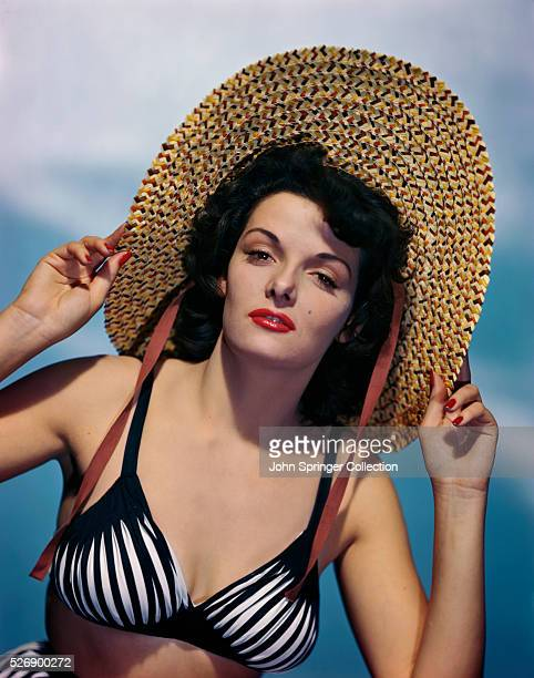 Actress Jane Russell wearing a black and white bikini top while holding the wide brim of a straw hat. Color publicity handout, slide.