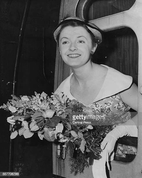 Actress Jane Wenham holding a bouquet of flowers and leaning out of a train carriage as she and the rest of the Old Vic Theatre Company prepare to...