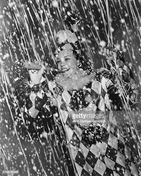 Actress Jane Wyman, dressed in a clown suit, is surrounded by confetti during a New Year celebration.