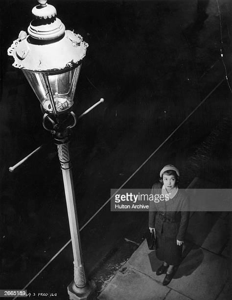 US actress Jane Wyman standing beside a lamppost in a scene from Alfred Hitchcock's film 'Stage Fright'