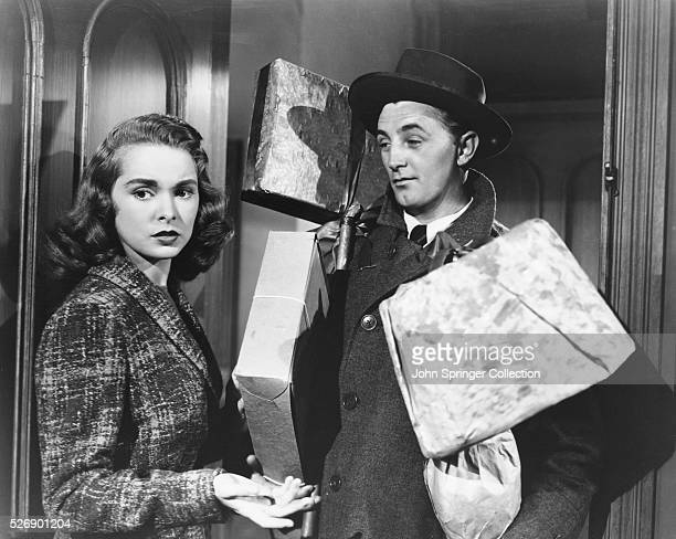 Actress Janet Leigh and actor Robert Mitchum holding wrapped packages in the 1949 film Holiday Affair. Mitchum plays the role of salesman Steve Mason...